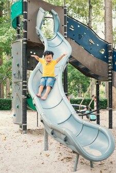 Mały chłopiec na placu zabaw ściąga rurę w dół, lato, szczęście, wakacje