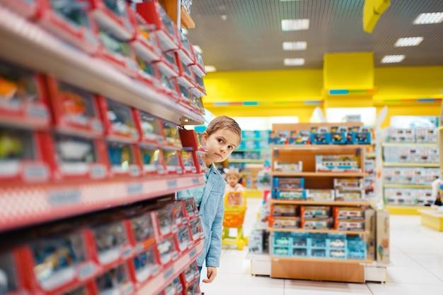 Mały chłopiec na półce w sklepie dla dzieci. syn wybiera zabawki w supermarkecie