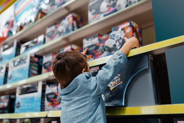 Mały chłopiec na półce w sklepie dla dzieci, widok z boku