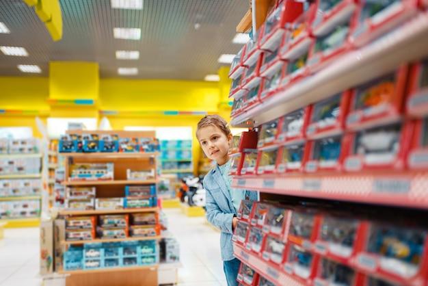 Mały chłopiec na półce w sklepie dla dzieci