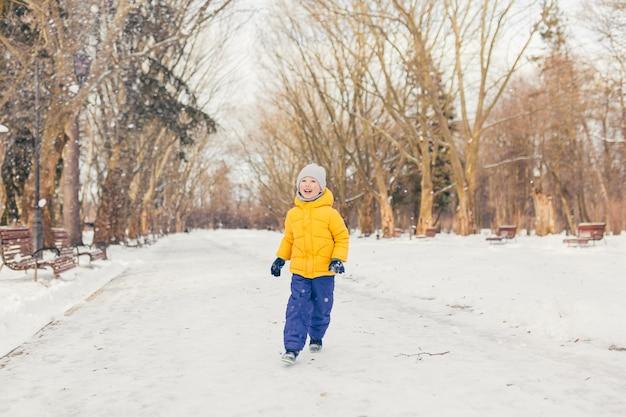 Mały chłopiec na spacerze w parku z rodziną zimą, bawiąc się i ciesząc się śniegiem