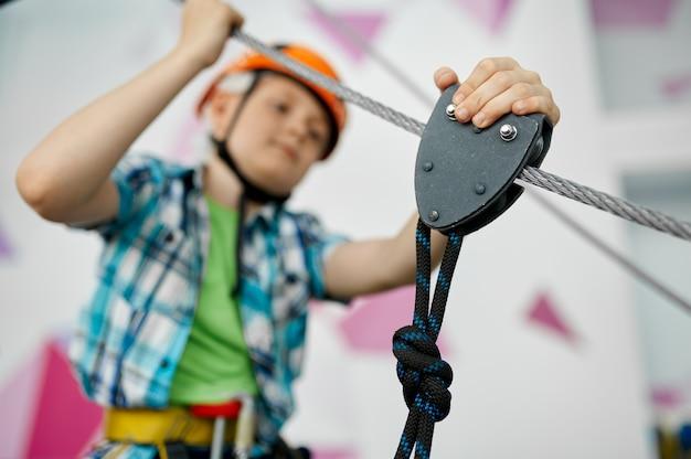Mały chłopiec na tyrolce, młody wspinacz w kasku