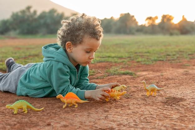 Mały chłopiec na zewnątrz, bawi się zabawkami