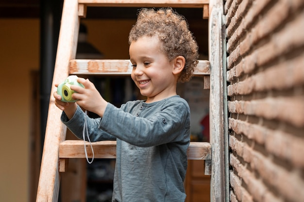 Mały chłopiec na zewnątrz z zabawką aparatu