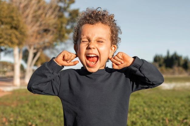 Mały chłopiec na zewnątrz zakrywający uszy
