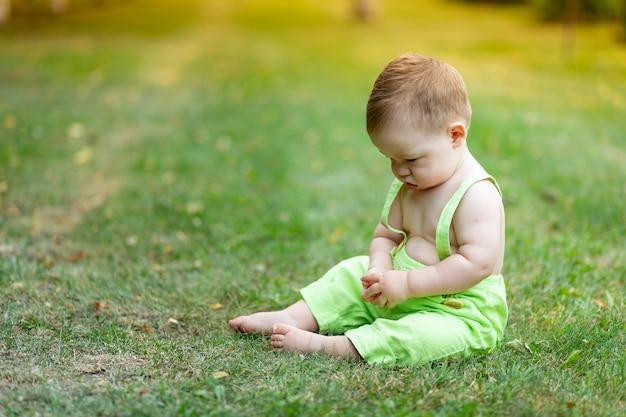 Mały chłopiec na zielonym trawniku latem boli i smutny chce płakać i patrzy w dół, miejsce na tekst.