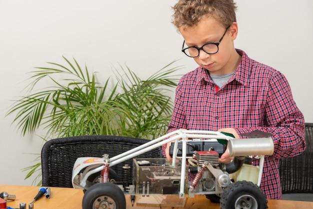 Mały chłopiec naprawiający w domu model samochodu sterowanego radiowo