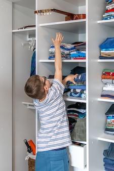 Mały chłopiec nie może zdjąć swojej gitary z górnej półki szafki.