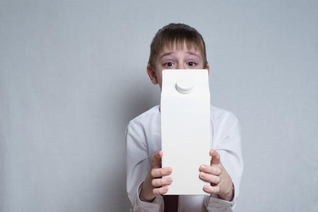 Mały chłopiec o blond włosach trzyma i pokazuje duże, białe opakowanie kartonowe