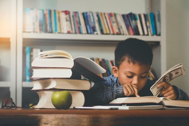 Mały chłopiec obcokrajowiec czytanie książki i gospodarstwa banknotów dolarowych z happy.
