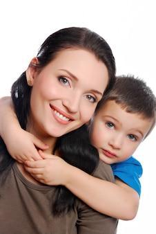 Mały chłopiec obejmując swoją piękną młodą matkę