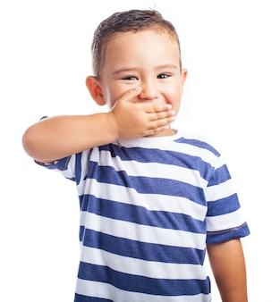 Mały chłopiec obejmującego usta śmiejąc