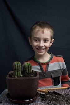 Mały chłopiec odłożył kaktusa z rośliny doniczkowej