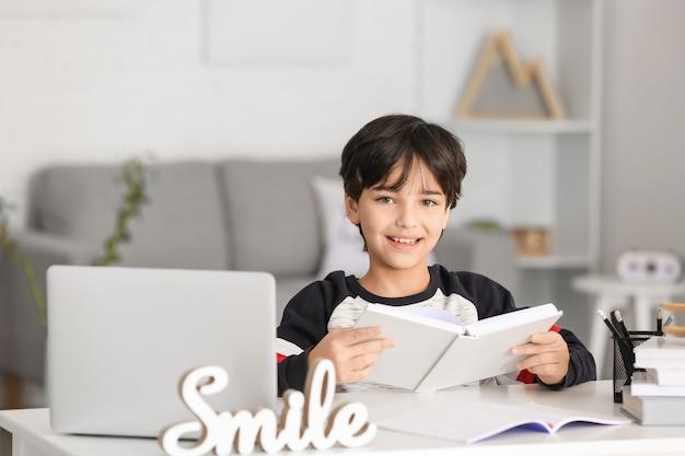 Mały chłopiec odrabia lekcje w pokoju