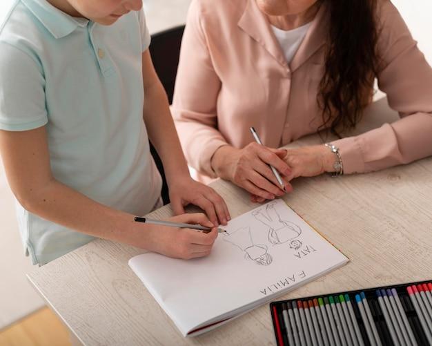 Mały chłopiec odrabia lekcje z babcią