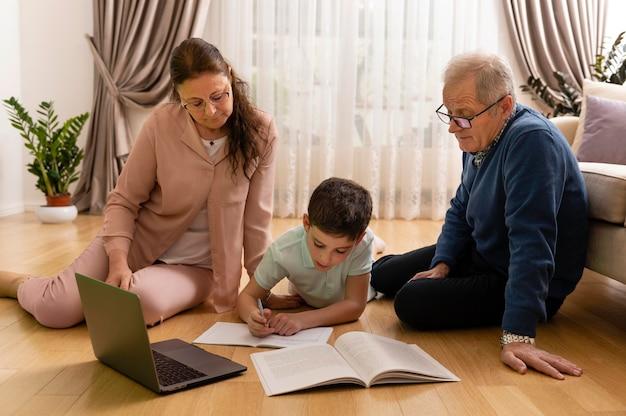 Mały chłopiec odrabia lekcje z dziadkami w domu