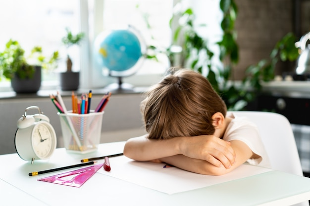 Mały chłopiec odrabiający pracę domową w domu przy stole przepracowanie pierwszoklasisty od studiowania stresu u