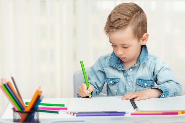 Mały chłopiec odrabiania lekcji, pisanie i malowanie