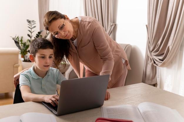 Mały chłopiec odrabiania lekcji z babcią na laptopie