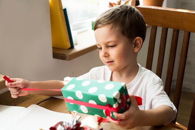 Mały chłopiec odwija prezent