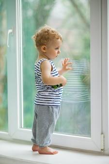Mały chłopiec ogląda deszcz przez okno