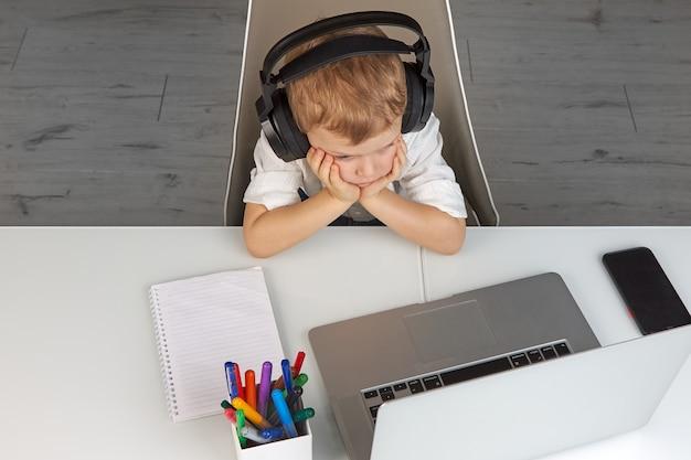 Mały chłopiec ogląda lekcje edukacji online na laptopie ze słuchawkami