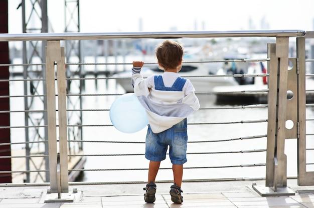 Mały chłopiec ogląda z ciekawością jachty zza płotu z ballun