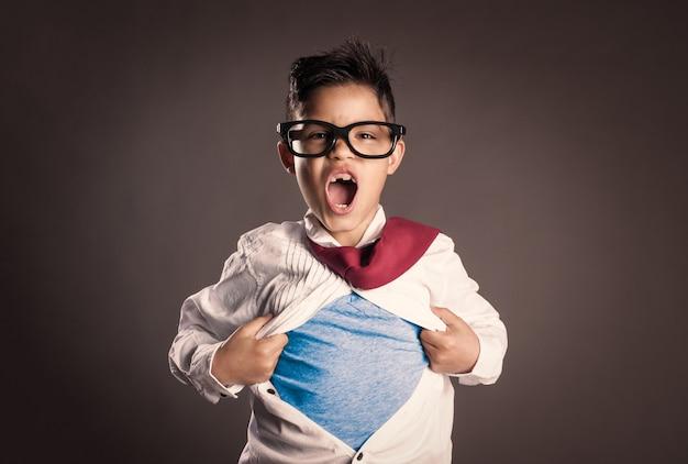 Mały chłopiec otwiera koszulę jak superbohater na szarym