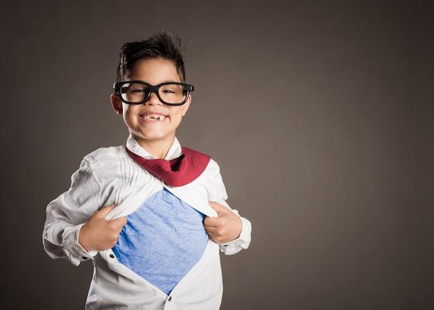 Mały chłopiec otwierający koszulę jak superbohater