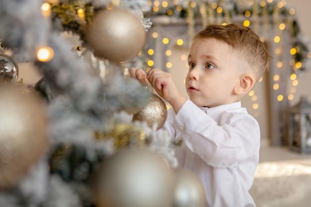 Mały chłopiec ozdabia choinkę na boże narodzenie.