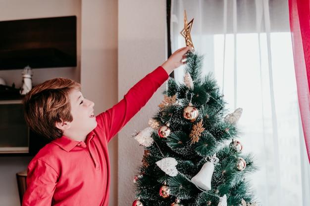 Mały chłopiec ozdabia choinkę w domu