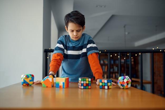 Mały chłopiec patrzy na kostki układanki. zabawka do treningu mózgu i logicznego umysłu, kreatywna gra