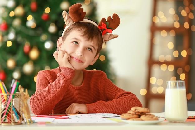 Mały chłopiec pisze list do świętego mikołaja w domu w wigilię bożego narodzenia