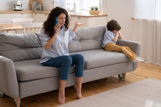 Mały chłopiec płacze, gdy mama kłóci się z tatą przez telefon