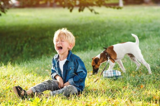 Mały chłopiec płacze i siedzi na ziemi w parku