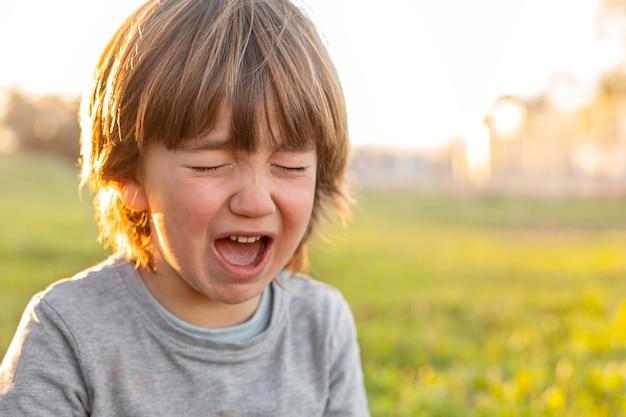 Mały chłopiec płacze na świeżym powietrzu