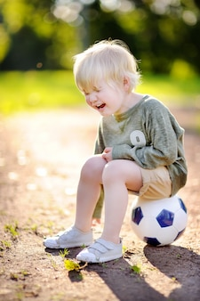 Mały chłopiec płacze po upadku podczas meczu piłki nożnej / piłki nożnej w letni dzień
