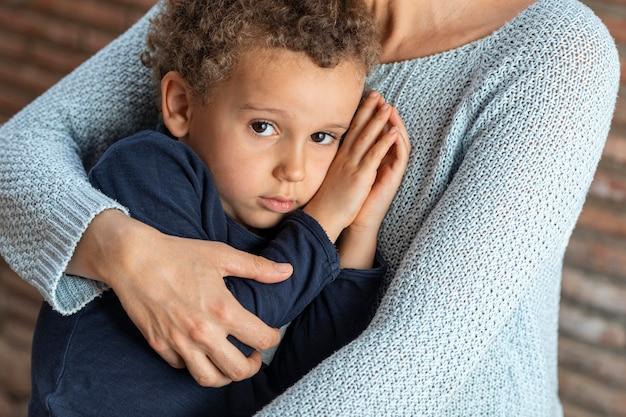 Mały chłopiec pocieszony przez matkę smutny