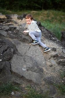 Mały chłopiec podbija górę.