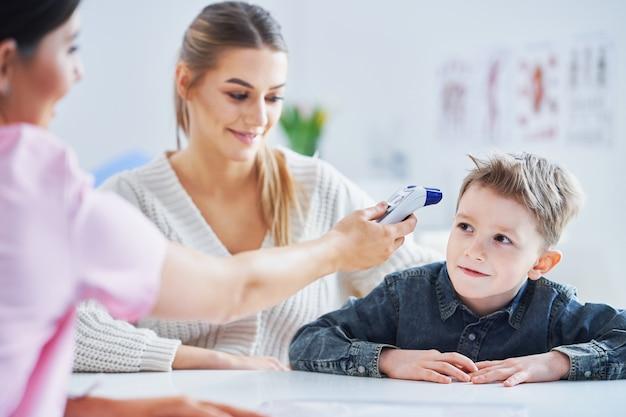 Mały chłopiec poddawany badaniom lekarskim przez pediatrę