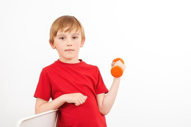 Mały chłopiec podnoszący hantle