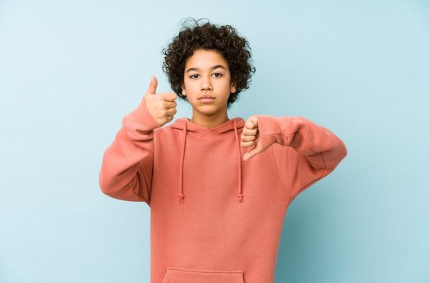 Mały chłopiec pokazuje kciuki w górę i w dół