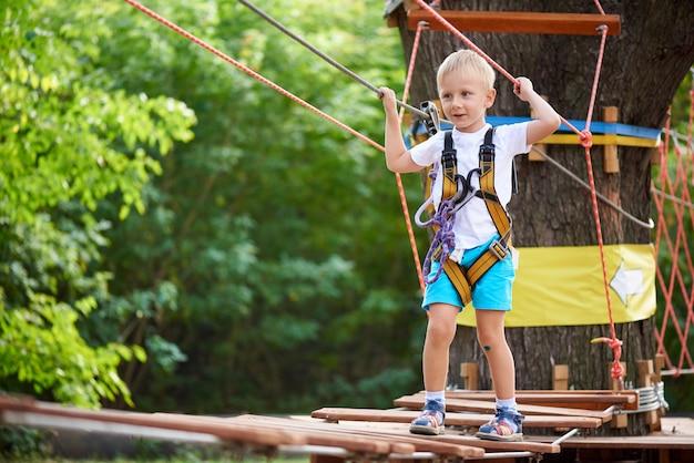 Mały chłopiec pokonuje przeszkodę w parku linowym.