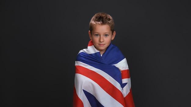 Mały chłopiec pokryty amerykańską flagą. kaukaskie 10-letnie dziecko uśmiecha się lekko.