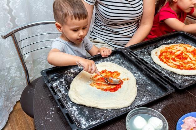 Mały chłopiec pomaga matce zrobić pizzę w domu