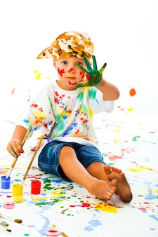 Mały chłopiec poplamiony farbą rysuje