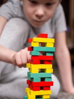 Mały chłopiec poszycia z kolorową drewnianą wieżą