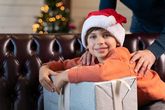 Mały chłopiec pozuje obok prezentu na boże narodzenie