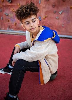 Mały chłopiec pozuje obok ścianki wspinaczkowej