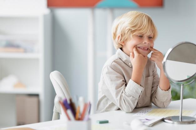 Mały chłopiec praktykujący terapię mowy